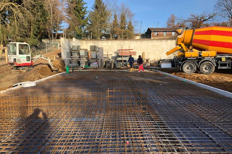 Ein Betonmischer steht bereit, um Beton ins Fundament zu gießen.