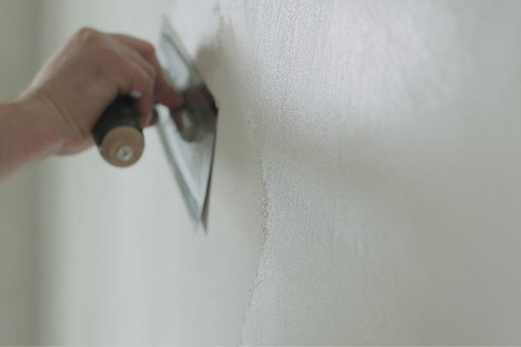 eine Wand wird mit Reibebrett verspachtelt